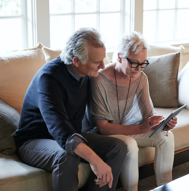 Couple using a tablet while sitting on their couch