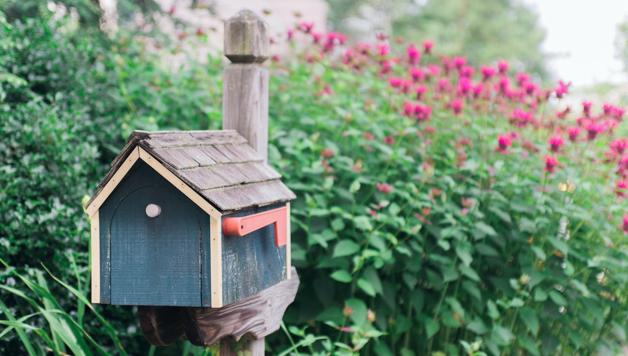 A house shaped mailbox in a garden